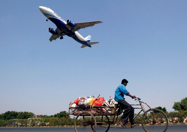 An IndiGo Airlines aircraft prepares to land as a man paddles his cycle rickshaw in Ahmedabad, India, October 26, 2015
