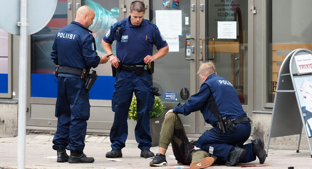 Police officers stand next to a person lying on the pavement in the Finnish city of Turku where several people were stabbed on August 18, 2017