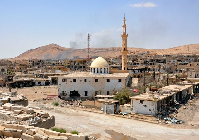 Smoke rising from buildings behind a mosque in the central Syrian town of Al-Sukhnah