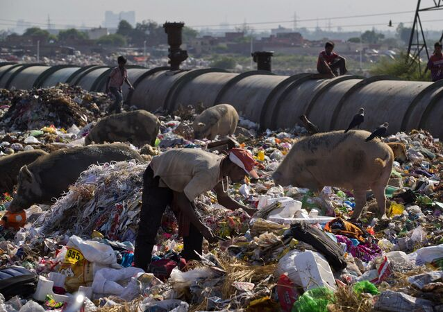 A man scavenges for reusable material in an open garbage in New Delhi, India