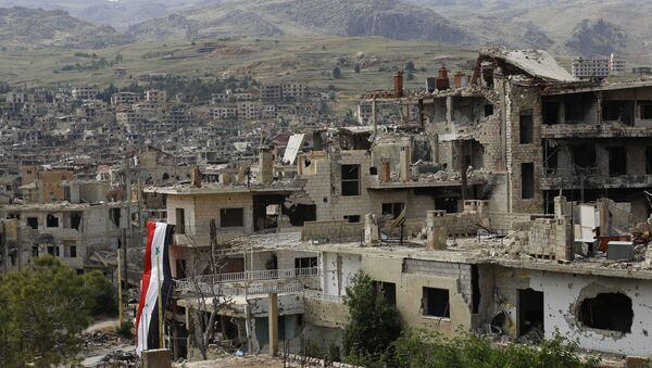 In this May 18, 2017, photo, a Syrian National flag hangs out of a damaged building at the mountain resort town of Zabadani in the Damascus countryside, Syria. - Sputnik International