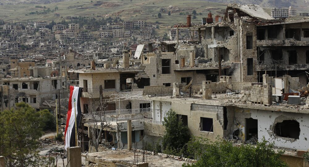 In this May 18, 2017, photo, a Syrian National flag hangs out of a damaged building at the mountain resort town of Zabadani in the Damascus countryside, Syria.