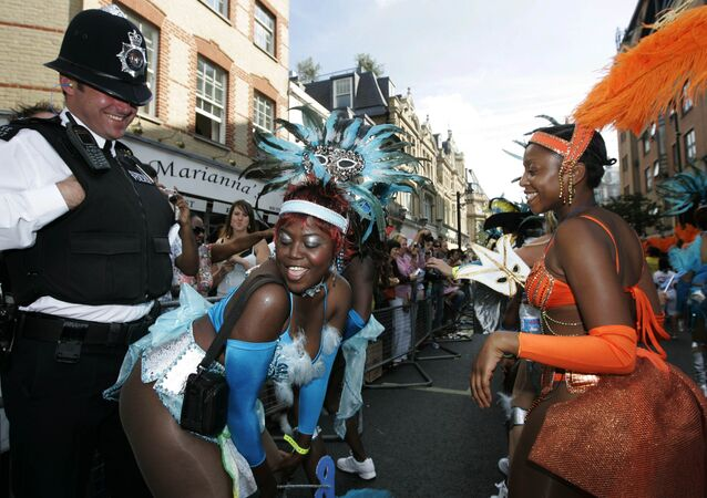 Participants in costumes dance in front of a British police officer during the Notting Hill Carnival in London, Monday Aug. 27, 2007.