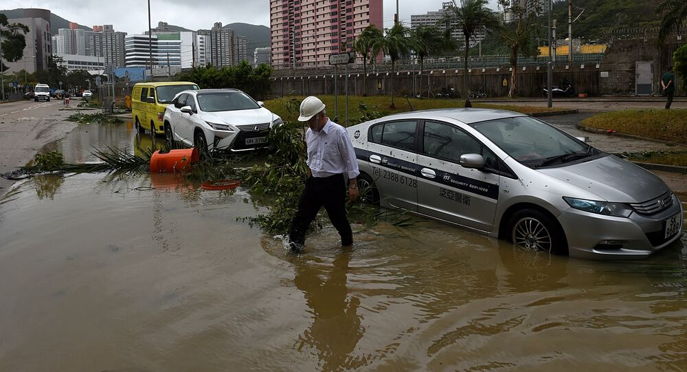 A man wades through floodwaters away from his car after heavy rains brought on by Typhoon Hato in Hong Kong on August 23, 2017