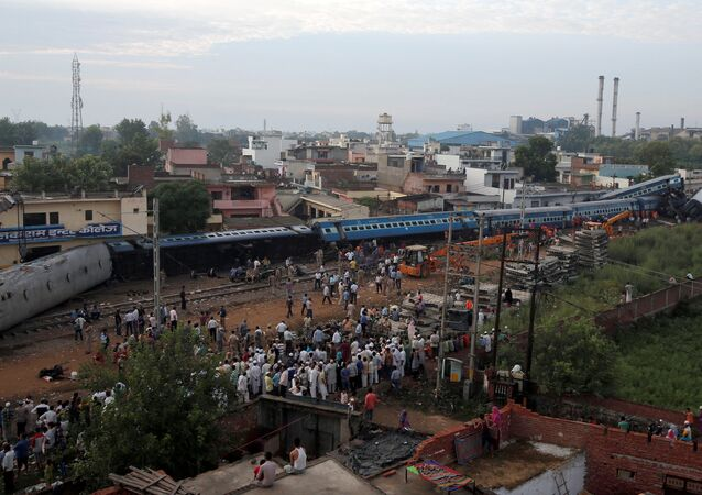 Rescue workers and onlookers stand next to derailed coaches of a passenger train at the site of an accident in Khatauli, in the northern state of Uttar Pradesh, India August 20, 2017