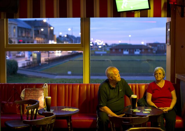 In this Wednesday, July 6, 2016 photo, a couple sit inside a pub at Great Yarmouth, East of England.