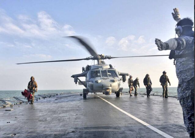 In this photo released by the Royal Malaysian Navy, a U.S. Navy helicopter lands to receive an unidentified body recovered by the Royal Malaysian Navy off the Johor coast of Malaysia, Wednesday, Aug. 23, 2017