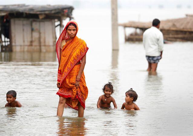 A woman walks through a flooded village in Motihari, Bihar State, India August 23, 2017.