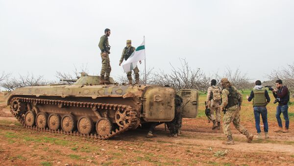 A picture taken on March 22, 2017 near the town of Maardes in the countryside of the central Syrian province of Hama, shows rebel fighters walking past an armoured vehicle carrying the flag of the Tahrir al-Sham rebel alliance - Sputnik International