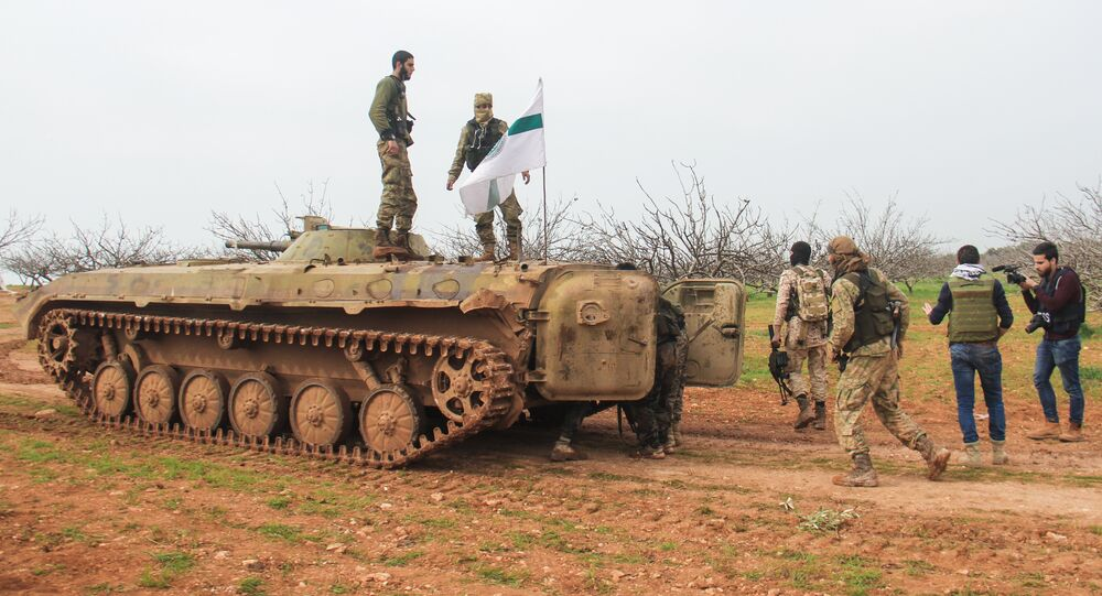A picture taken on March 22, 2017 near the town of Maardes in the countryside of the central Syrian province of Hama, shows rebel fighters walking past an armoured vehicle carrying the flag of the Tahrir al-Sham rebel alliance