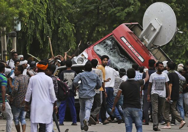 Dera Sacha Sauda sect members overturn an OB van on the streets of Panchkula, India, Friday, Aug. 25, 2017