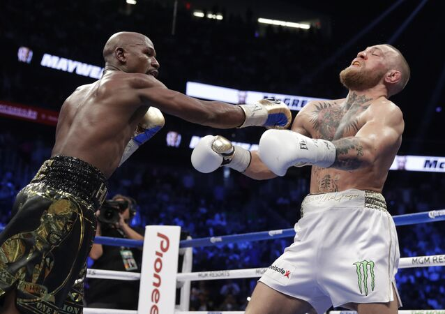Floyd Mayweather Jr. hits Conor McGregor in a super welterweight boxing match Saturday, Aug. 26, 2017, in Las Vegas.
