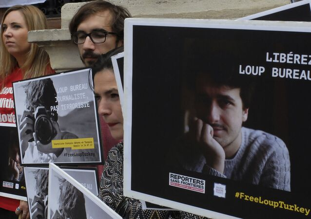 Activists from Reporters Without Borders carry posters in a show of support to French freelance journalist Loup Bureau