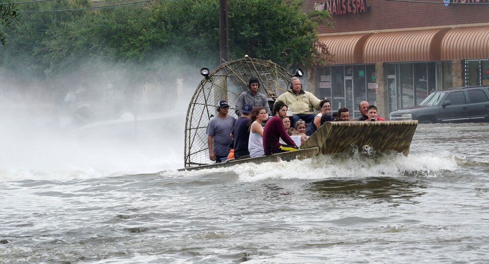 People are rescued from flood waters from Hurricane Harvey on an air boat in Dickinson, Texas