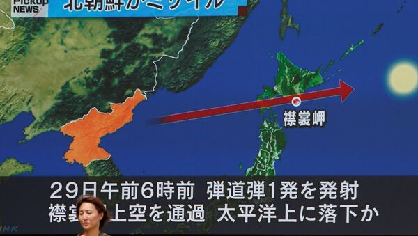 A woman walks past a large TV screen showing news about North Korea's missile launch in Tokyo, Japan, August 29, 2017. - Sputnik International