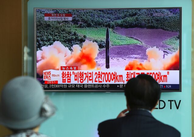 People watch a television news screen showing file footage of a North Korean missile launch, at a railway station in Seoul on August 29, 2017.