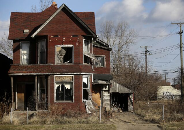 Curtains flap outside the broken window of an abandoned home December 31, 2014 in Detroit, Michigan.