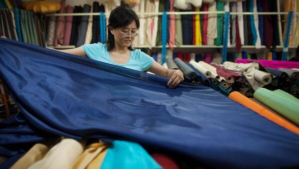 A vendor prepares rolls of silk at her textile and fabric shop in Beijing - Sputnik International