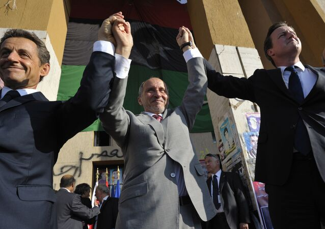 French President Nicholas Sarkozy, left, Libya's NTC leader Mustafa Abdul-Jalil, center, and British Prime Minister David Cameron, right, gesture during their visit to Benghazi, Libya, Thursday, Sept. 15, 2011.