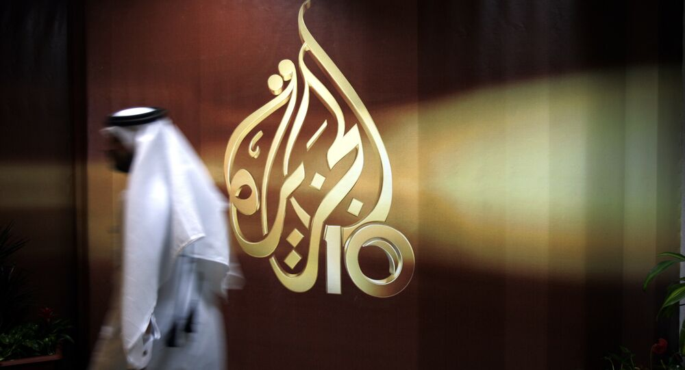 A Qatari employee of Al Jazeera Arabic language TV news channel passes by the logo of Al Jazeera in Doha, Qatar. (File)