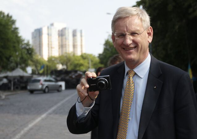Swedish Foreign Minister Carl Bildt, holds a camera during his walk in central Kiev, Ukraine, Friday, May 16, 2014