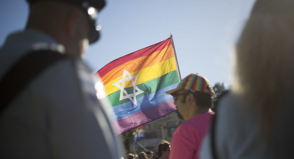 Israeli police officers watch as people take part in the annual gay pride parade in central Jerusalem, Thursday, July 21, 2016.