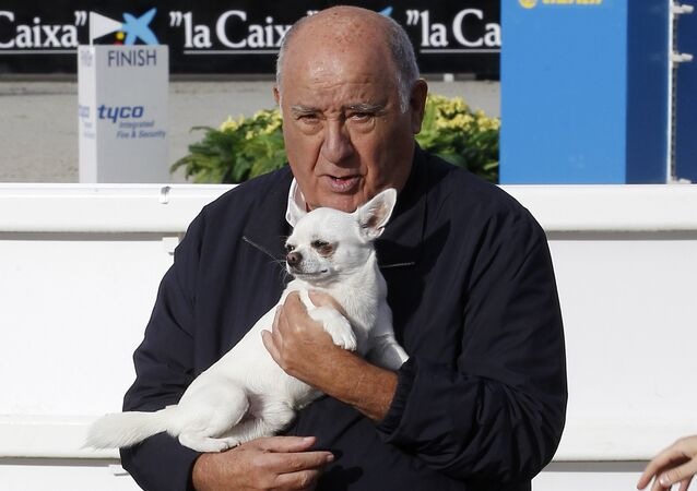 In this July 28, 2013 photo, Amancio Ortega Gaona, founding shareholder of Inditex fashion group, best known for its chain of Zara clothing and accessories retail shops, holds a dog during the Casas Novas International Jumping Show in Arteixo, A Coruña, in the Galicia region of northwest Spain.