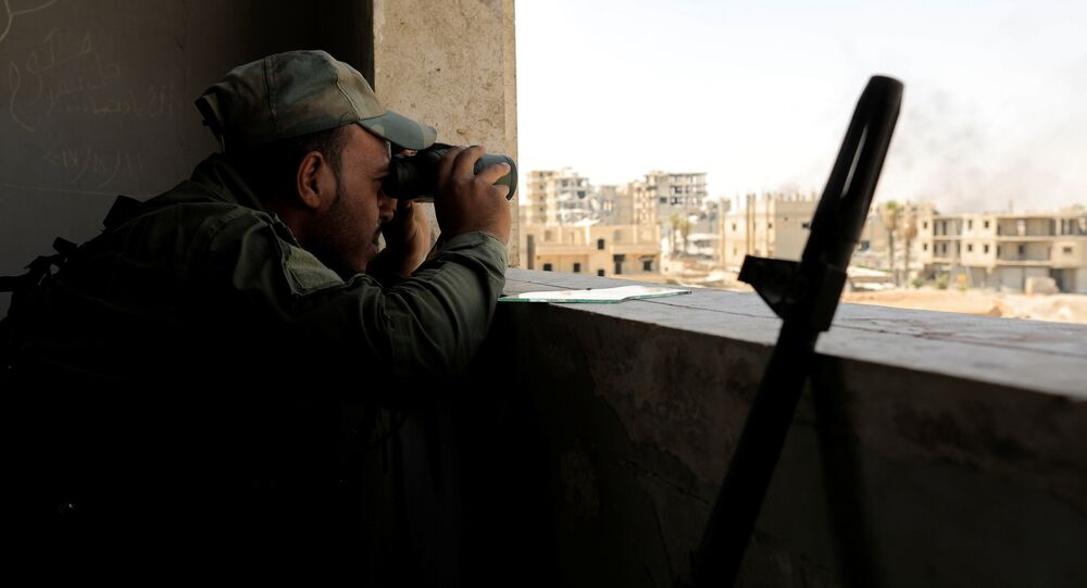 A member of Syrian Democratic Forces keeps watch during the fighting with Islamic State militants in Al Senaa, a district Raqqa, Syria August 11, 2017