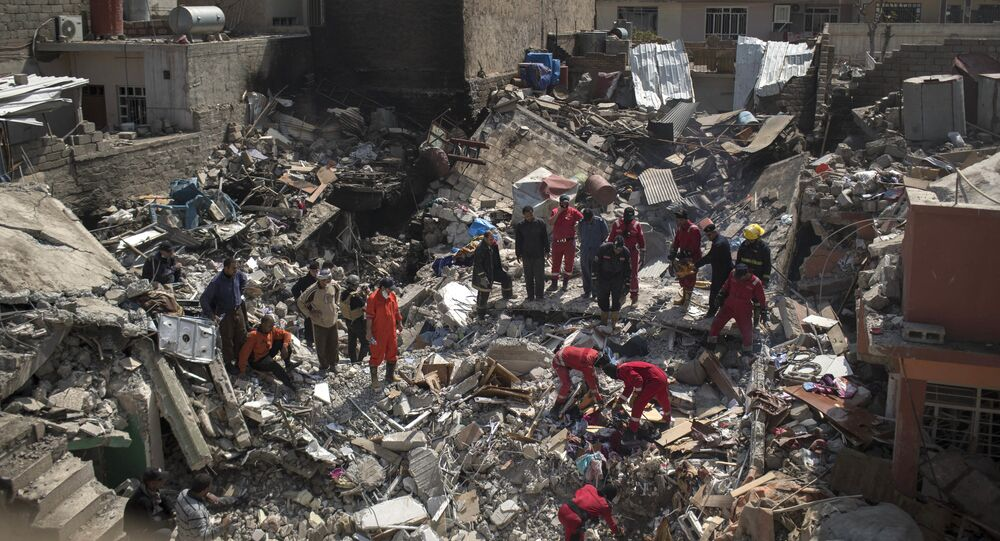 In this Friday, March 24, 2017 photo, civil protection rescue teams work on the debris of a destroyed house to recover the body of people killed during fighting between Iraqi security forces and Islamic State militants on the western side of Mosul, Iraq