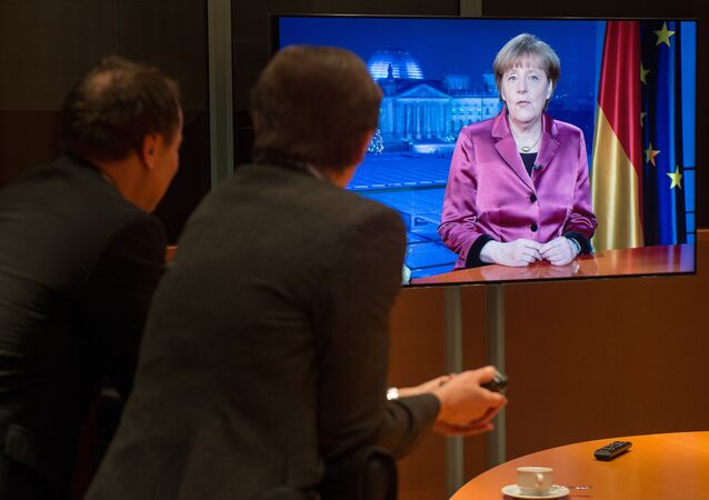 Employees of the chancellery and tv crew watch on a screen as German Chancellor Angela Merkel records her annual New Year's speech at the Chancellery in Berlin on December 30, 2014