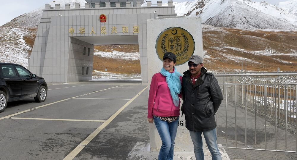 In this photograph taken on September 29, 2015, a Chinese woman (L) poses for a photograph with a Pakistani man at the Pak-China Khunjerab Pass, the world's highest paved border crossing at 4,600 metres above sea level