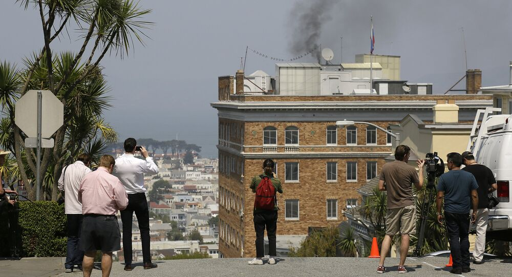 People stop to watch black smoke coming from the roof of the Consulate-General of Russia Friday, Sept. 1, 2017, in San Francisco