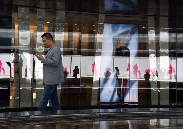 A man walks past stores in a shopping mall in Beijing on the second day of the National Day holidays on October 2, 2015