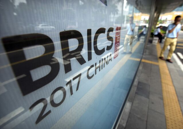 A man stands near a billboard advertising the 2017 BRICS Summit at a bus shelter in Xiamen in southeastern China's Fujian Province, Saturday, Sept. 2, 2017