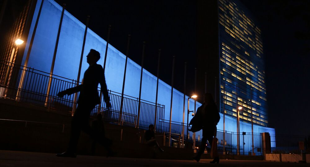 Pedestrians walk by United Nations Headquarters, lit up in blue light, a day in advance of the 70th Anniversary of the U.N., in New York City. File Photo.