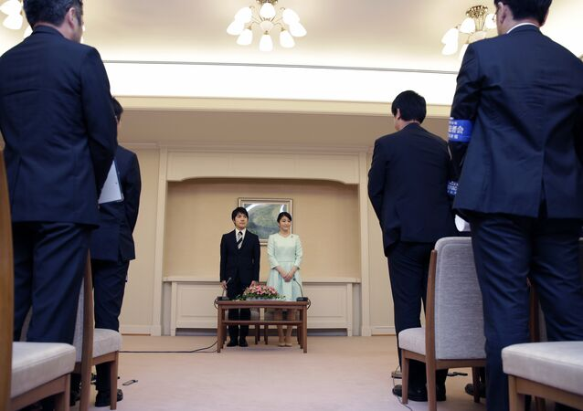 Japan's Princess Mako, center right, the elder daughter of Prince Akishino and Princess Kiko, and her fiance Kei Komuro, center left, greet the reporters at the end of their press conference at Akasaka East Residence in Tokyo, Sunday, Sept. 3, 2017