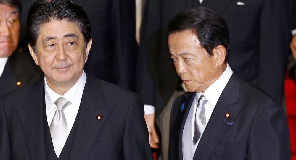 In this Aug. 3, 2017 photo, Japan's Prime Minister Shinzo Abe, left, and Deputy Prime Minister Taro Aso leave after an official photo session with Abe's new Cabinet at the prime minister's official residence in Tokyo