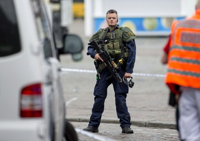 An armed police officer secures the area following a multiple stabbing attack on the Market Square in Turku, Finland, Friday Aug. 18, 2017