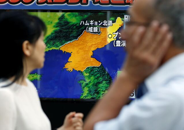 People walk past a street monitor showing a news report about North Korea's nuclear test, in Tokyo, Japan, September 3, 2017