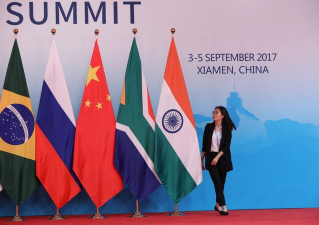 A staff worker walks past the national flags of Brazil, Russia, China, South Africa and India before a group photo during the BRICS Summit at the Xiamen International Conference and Exhibition Center in Xiamen, southeastern China's Fujian Province, China September 4, 2017