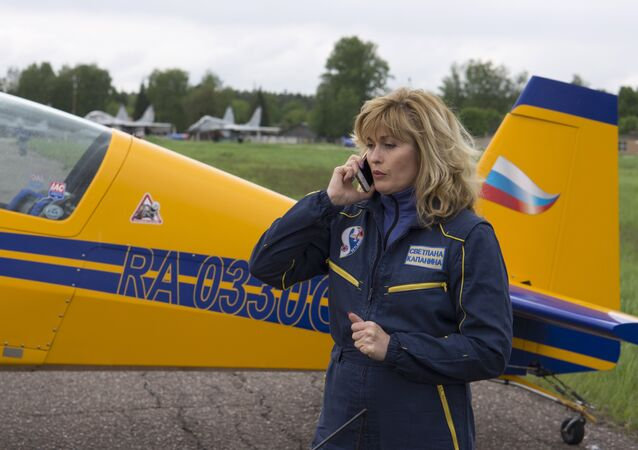 Russian pilot Svetlana Kapanina stands next to her plane following her performance at an air show at the Kubinka air base outside Moscow, Russia