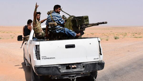 Syrian pro-government forces sit in the back of an armed vehicle in Bir Qabaqib, more than 40 kilometres west of Deir Ezzor, after taking control of the area on their way to Kobajjep in the ongoing battle against Islamic State (IS) group jihadists on September 4, 2017 - Sputnik International