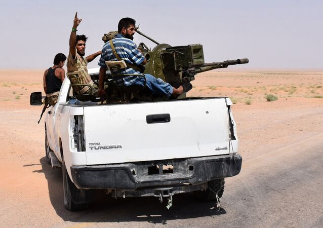 Syrian pro-government forces sit in the back of an armed vehicle in Bir Qabaqib, more than 40 kilometres west of Deir Ezzor, after taking control of the area on their way to Kobajjep in the ongoing battle against Islamic State (IS) group jihadists on September 4, 2017