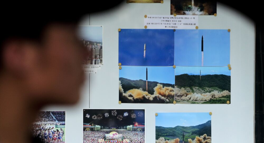 A man drives his car past a display board showing photos of ballistic missile launches in North Korea outside the North Korean Embassy in Beijing