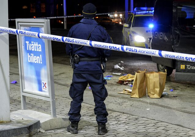 A police officer stands inside a roped off an area on a gas station in Fittja, Sweden, where a man was found severely injured in a minivan after being shot at when taking part in a pro-Kurdish demonstration Saturday, Feb. 13, 2016