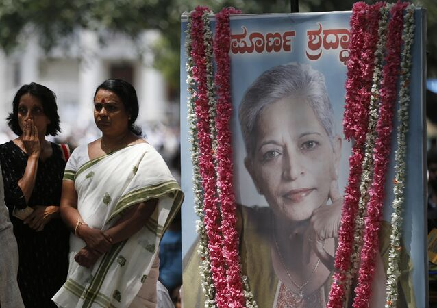Mourners stand next to a portrait of Indian journalist Gauri Lankesh during the public viewing of her body in Bangalore, India, Wednesday, Sept. 6, 2017.