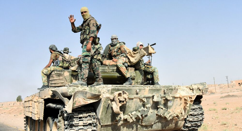 Members of the Syrian government forces ride on a tank, in the village of Kobajjep on the southwestern outskirts of Deir Ezzor province, on September 6, 2017, during the ongoing battle against Islamic State (IS) group jihadists.