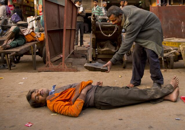 In this Friday, Dec. 12, 2014 photo, a drunk man offers his shoes to his colleague who passed out after consuming alcohol in New Delhi, India