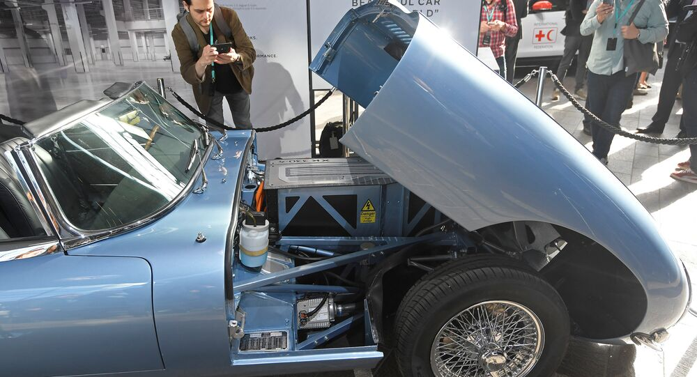A visitor views a classic Jaguar E-Type modified with an electric engine on display at the Jaguar Land Rover 'Tech Fest' in London
