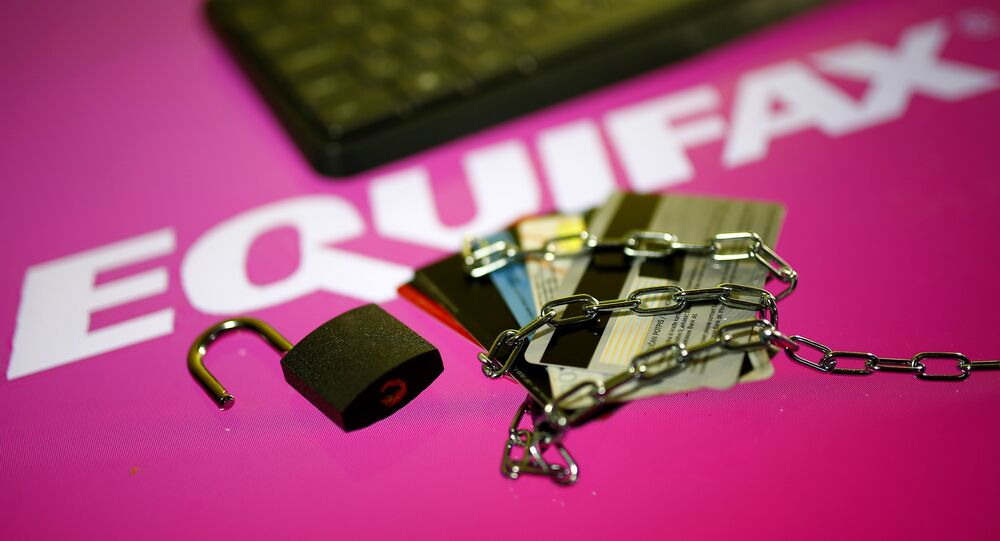 Credit cards, a chain and an open padlock is seen in front of displayed Equifax logo in this illustration taken September 8, 2017